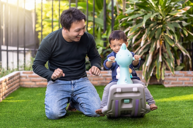 Asian single dad with son are playing together when living in front lawn for self learning