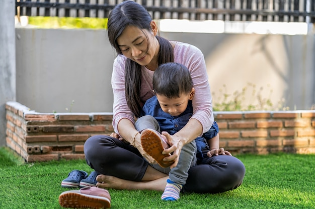 Asian single mom ware shoes to son on front lawn of modern house for self learning or home school