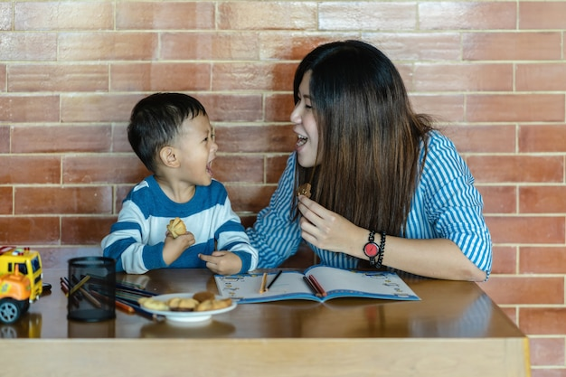 Asian single mom with son are drawing and eating cookie together when living in loft house