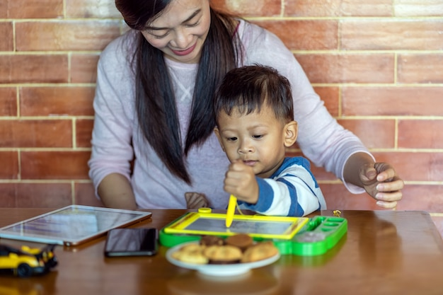 Asian single mom with son drawing