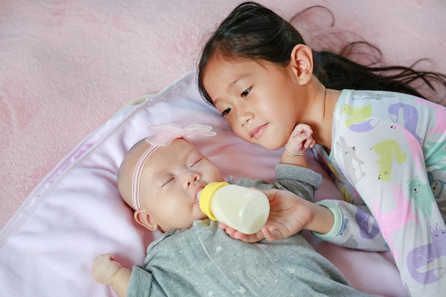 Asian sister feeding newborn baby girl with milk bottle on the bed.