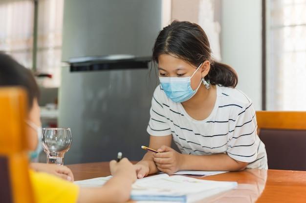 弟の宿題を教える保護マスクのアジアの姉妹