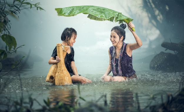 Asian sister in the rain, countryside of thailand