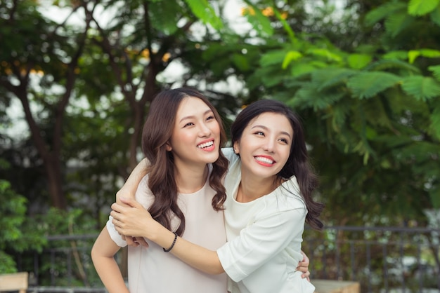 Азиатские сестры обнимаются и улыбаются в парке.