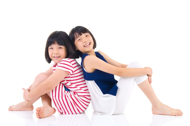 Asian sisters sitting on the floor