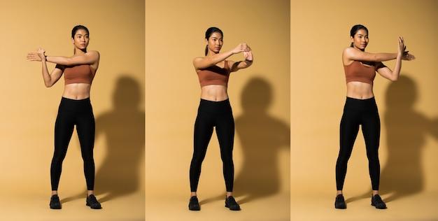 アジアンスリムフィットネス女性エクササイズウォームアップストレッチアームレッグ、スタジオ照明イエローベージュマスタード背景シャドウコピースペース、コンセプト女性ができるアスリートスポーツ6パック