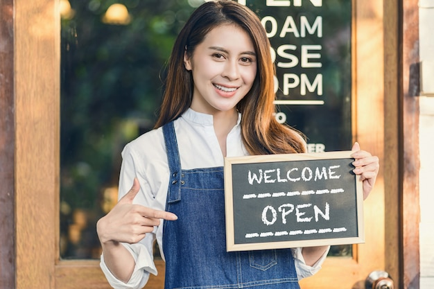 Asian small business owner hands holding and showing the chalkboard with welcome open sign in