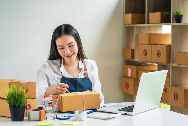아시아의 소기업 소유자는 집에서 소포 상자를 사용하여 온라인 판매로 고객에게 소포를 배달하기 위해 주소를 기록하는 펜을 들고 있습니다.