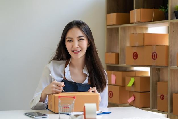 아시아 소기업 소유자는 소포 상자를 사용하여 온라인 판매 고객에게 소포를 배달하기 위해 주소를 기록하기 위해 펜을 들고 카메라를 바라보고 있습니다.