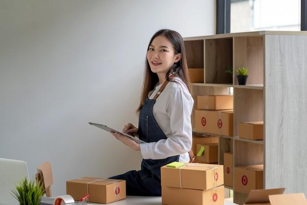 自宅の小包ボックスで顧客にそれらを配達する前に、オンラインで製品のタブレットを保持しているアジアの小さな実業家。カメラを見てください。