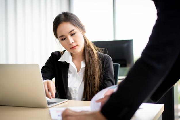 アジアのスマートなビジネスマンやビジネスウーマンが会議室で一緒に話して