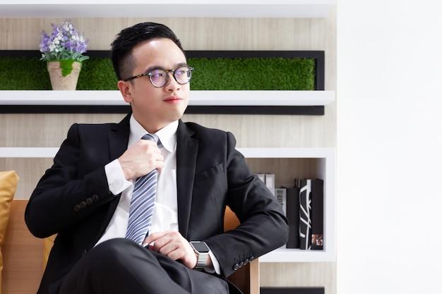 リビングルームで休んでアジアのスマートビジネスマン。