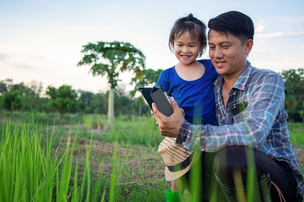 家族の有機農場で屋外でデジタルタブレットを使用して彼の幸せな小さな女の子の娘とアジアのスマート農家の父。