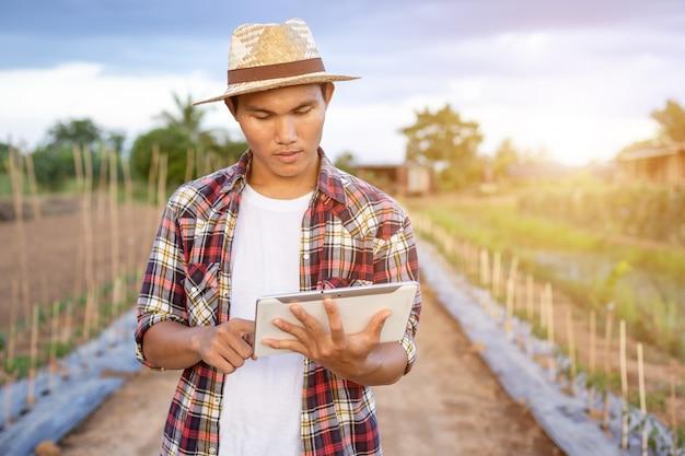 Asian smart farmer holding tablet in his organic farm.