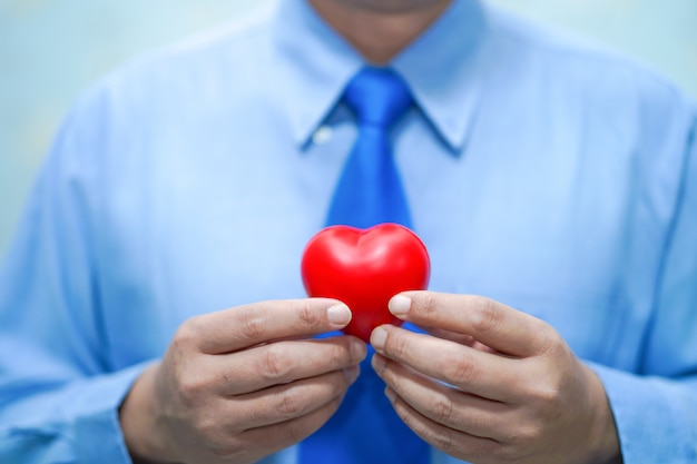 赤いハートを保持しているアジアのスマート男医師:健康的な強い医療概念。