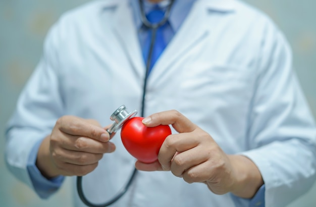 赤いハートを保持しているアジアのスマート男医師