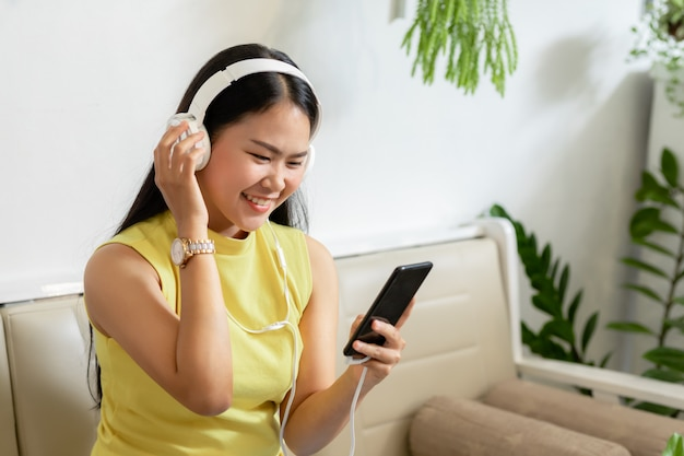 Asian smiling girl student wear wireless headphone study online with skype teacher in a coffee shop,