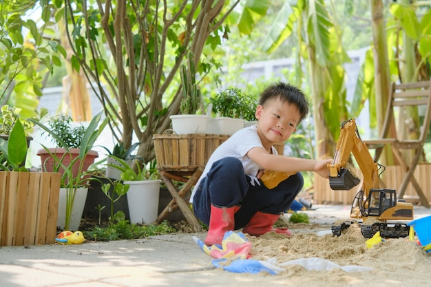 Asian smiling kid playing with sand toys and toy construction machinery in backyard home garden