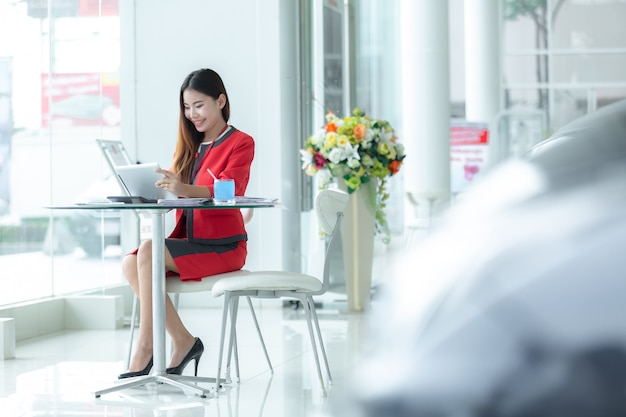 Asian smiling successful businesswoman in suit talking on phone using tablet sitting at of