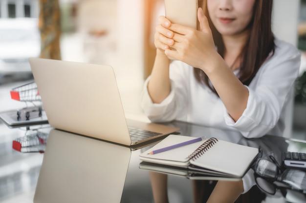 Азиатская усмехаясь женщина держа телефон и используя портативный компьютер к ходить по магазинам онлайн. красивая девушка текстовых сообщений на телефон.
