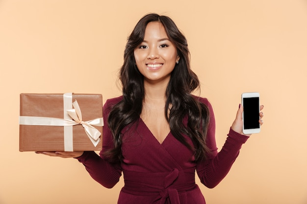 Asian smiling woman in maroon dress demonstrating present box with smartphone as gift being isolated over peach background