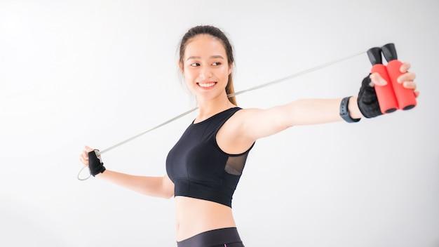 白い壁フィットネス背景に縄跳びでアジアの笑顔の女性運動します。