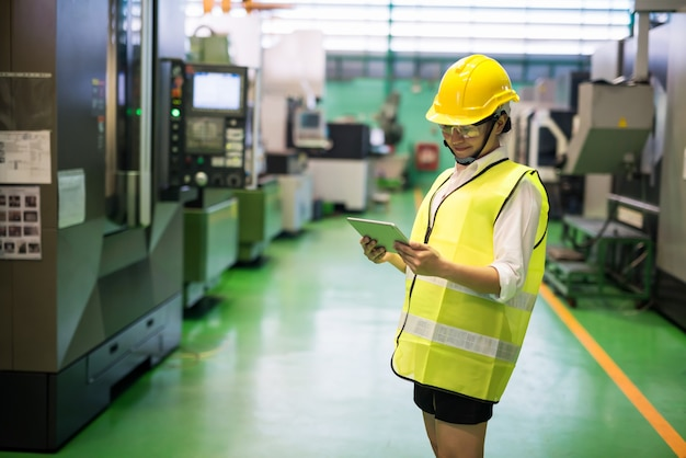 Asian smiling worker in hardhat using tablet to check transistor microchip machines in factory