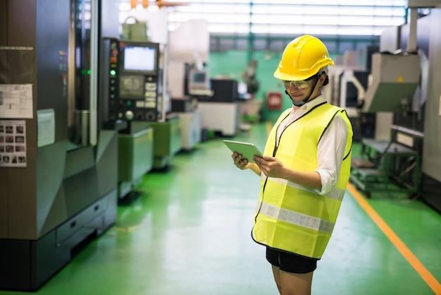공장에서 트랜지스터 마이크로칩 기계를 확인하기 위해 태블릿을 사용하는 안전모를 쓴 아시아인 웃는 노동자 프리미엄 사진