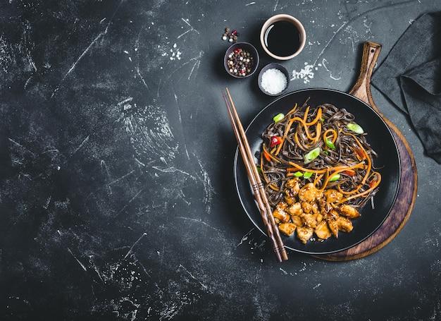 アジアのそば、鶏肉、野菜、暗い背景。テキスト用のスペース。