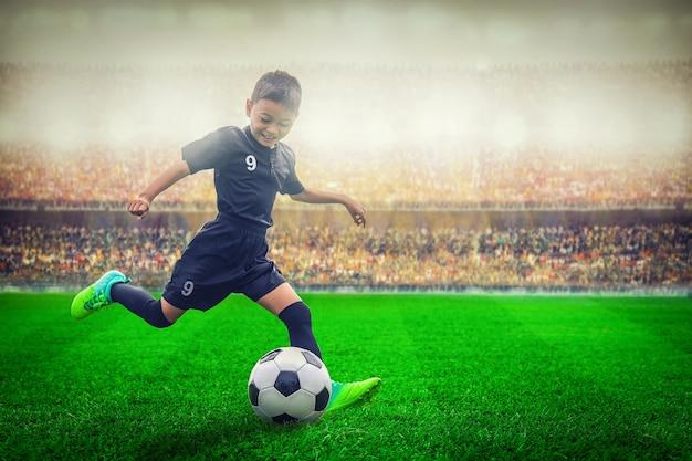 Asian soccer kid kicking football in the stadium