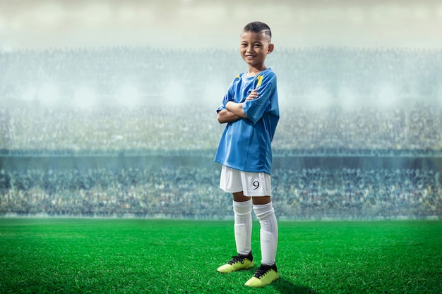 Asian soccer kids player in blue jersey standing and pose to camera in the stadium