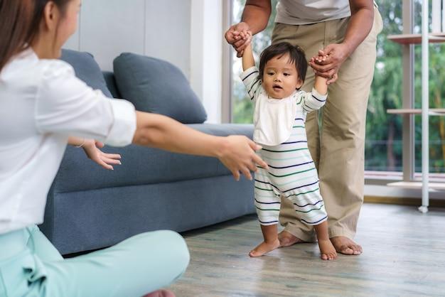 最初の一歩を踏み出すアジアの息子の赤ちゃんは彼の母親に向かって歩きます。父親の助けを借りて歩くことを学び、家で優しく歩く方法を教える幸せな小さな赤ちゃん