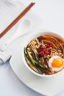 Asian soup near spoon and chopsticks