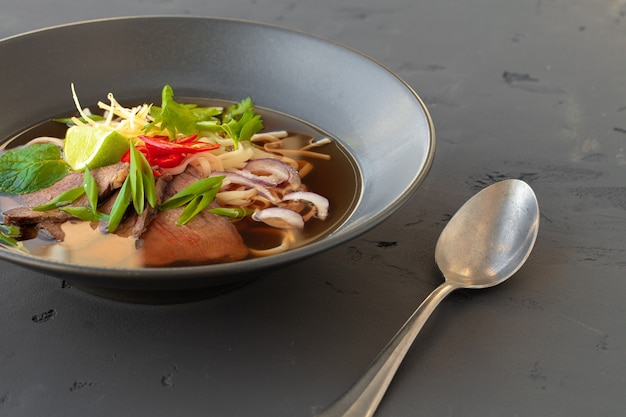 Asian soup ramen served in black bowl on gray table close up