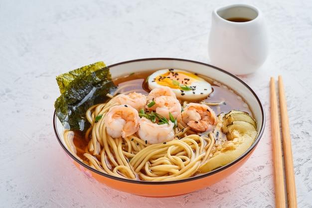 Asian soup with noodles, ramen with shrimps, miso paste, soy sauce.