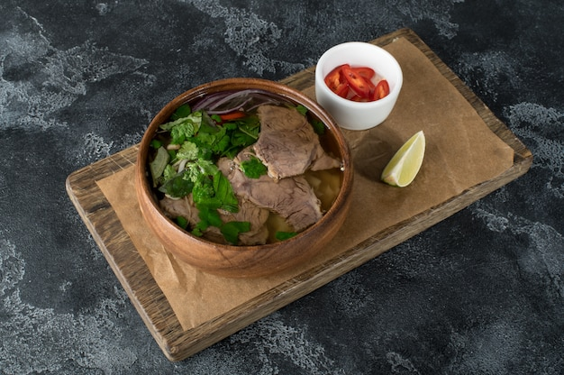 Asian soup in a wooden plate, pho bo soup, flat lay