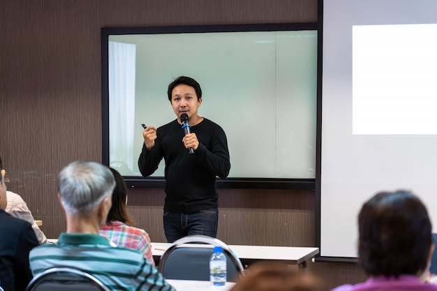 Asian speaker or lecture with casual suit on the stage in front of the room presenting