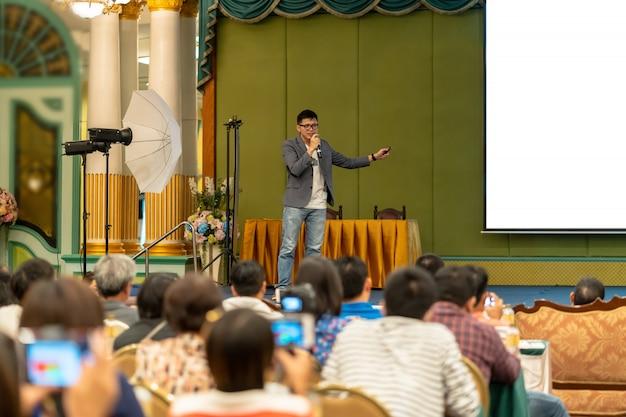 무대에 캐주얼 슈트가있는 아시아 스피커가 컨퍼런스 홀에서 화면을 제시합니다.