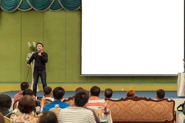 Asian speaker with casual suit on the stage