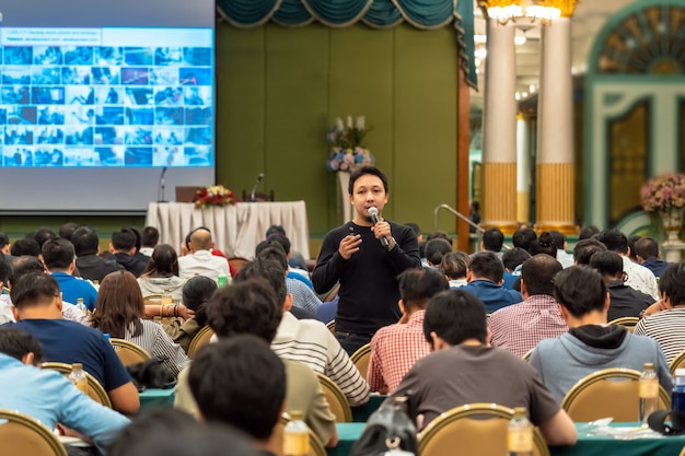 Asian speaker with casual suit standing and giving the knowledge with audience in the conf