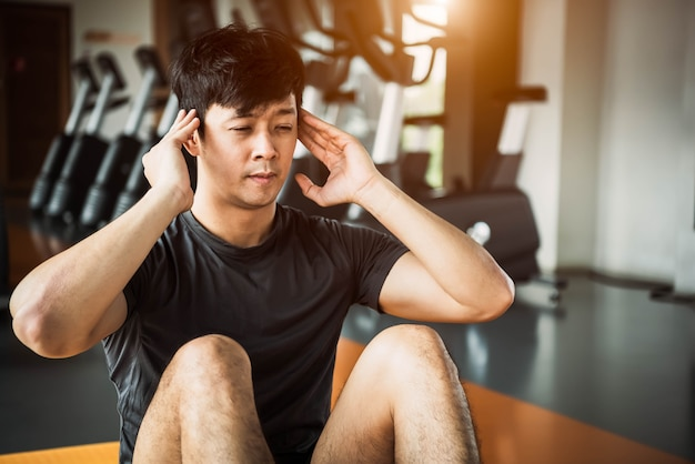 Asian sport man doing crunch or sit up posture on yoga mat in fitness gym