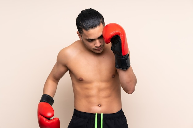 Asian sport man isolated on beige background with boxing gloves