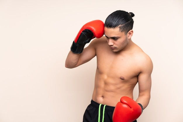 Asian sport man isolated on beige with boxing gloves