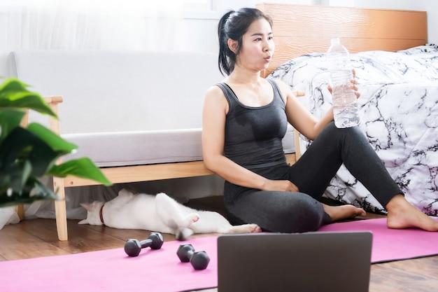 물 한 병으로 운동을 한 후 휴식을 취하는 아시아 스포츠 여성