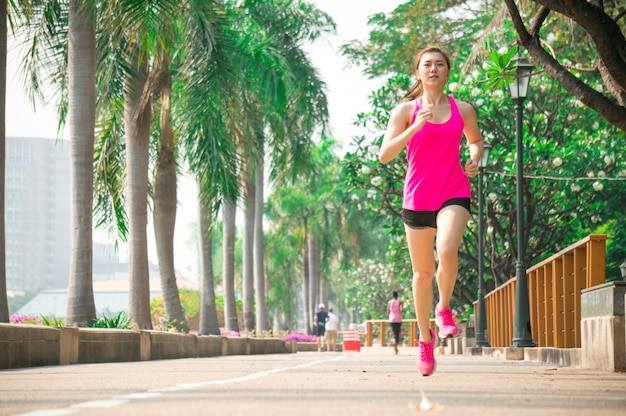 Asian sport woman run and exercise in park outdoor