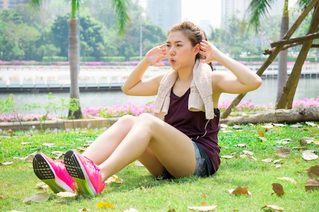 Asian sport woman sit up in park