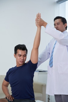 Asian sportsman getting physiotherapy at clinic