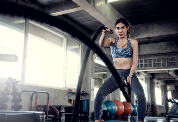 Asian sportswoman fit training with battle rope in fitness gym. sport and workout motivati