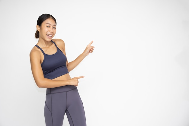 Asian sporty girls standing and pointing finger to the side blank copy space
