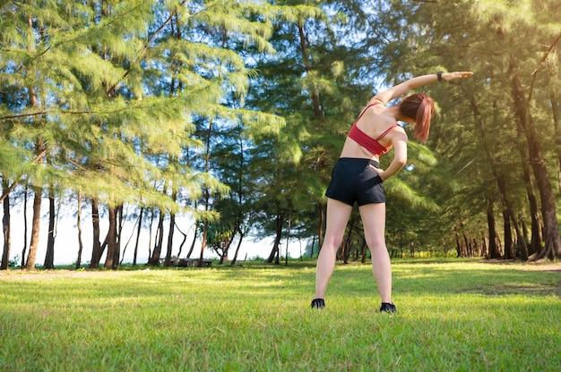 アジアのスポーティな女性が朝に運動してストレッチ